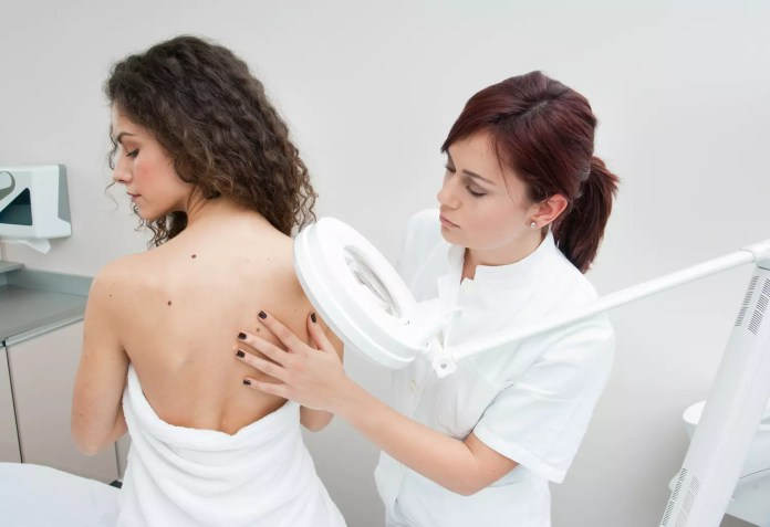 dermatologist doctor inspecting woman skin for moles and melanoma. DepositPhotos 1500x1027
