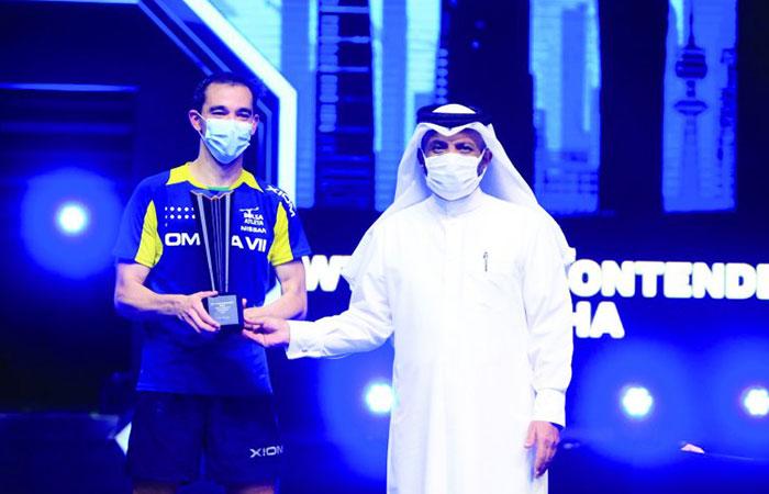 Qatar Table Tennis Association President Khalil Ahmed Al Mohannadi presenting the WTT trophy to WTT Star Contender Doha 2021 men's singles champion Hugo Calderano of Brazil at Lusail Sports Arena