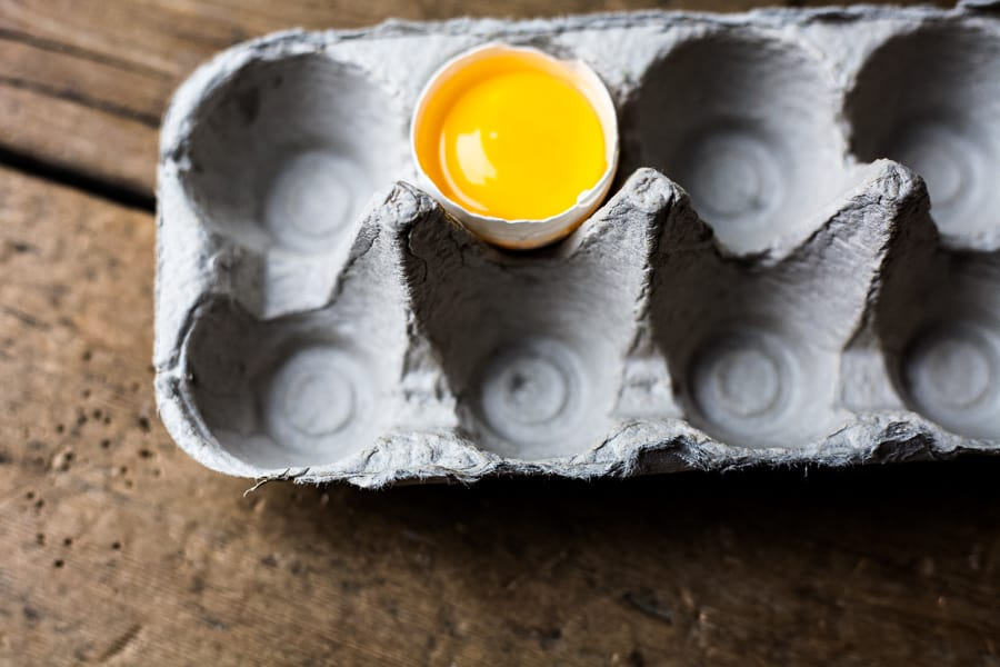 cracked egg in an empty egg carton