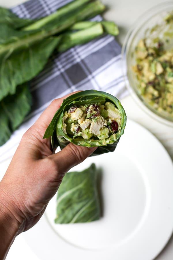 hand holding chicken salad collard green wrap