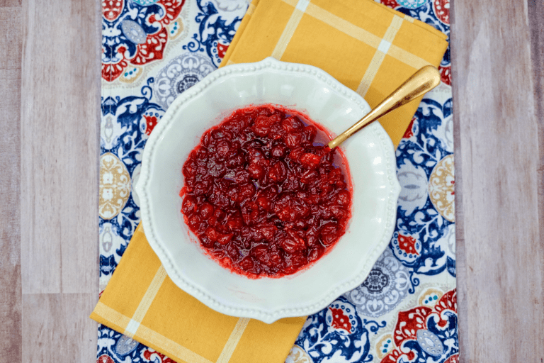 red cranberry sauce sitting in white bowl with gold spoon