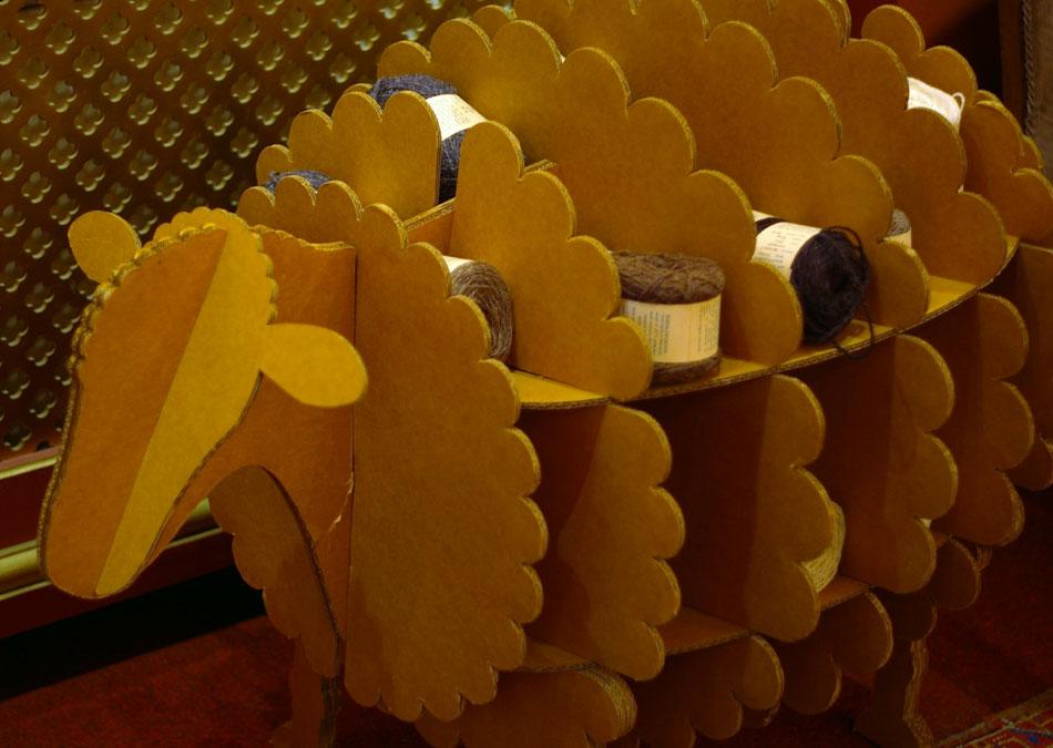 Shetland Organics cardboard yarn stand, shaped like a sheep and bearing balls of organic Shetland Wool in sheepy shades!