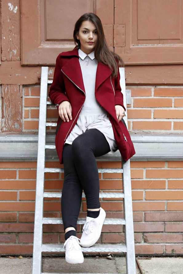 Dorie is sitting on a ladder, wearing a red coat, black legging, a grey dress and white shoes