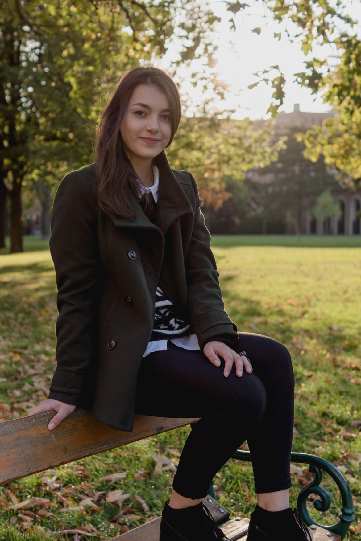 Dorie sitzt auf einer Parkbank und trägt einen grünen H&M Kurzmantel und schwarze Mint&Berry Schuhe, sowie einen schwarzen Pullover und Hose