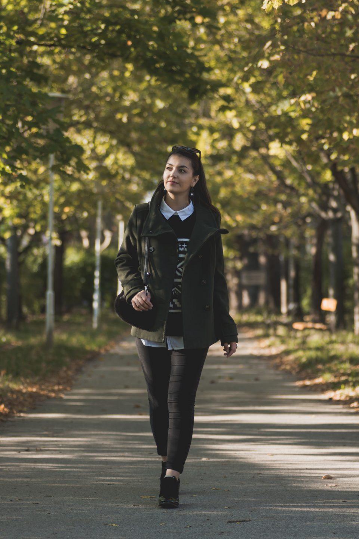 Dorie trägt einen schwarz-weißen Pullover mit weißem Hemd, einem grünen Kurzmantel, schwarze Hose, schwarze Lack-Schuhe und einer Fake-Fur Handtasche und läuft eine Allee entlang