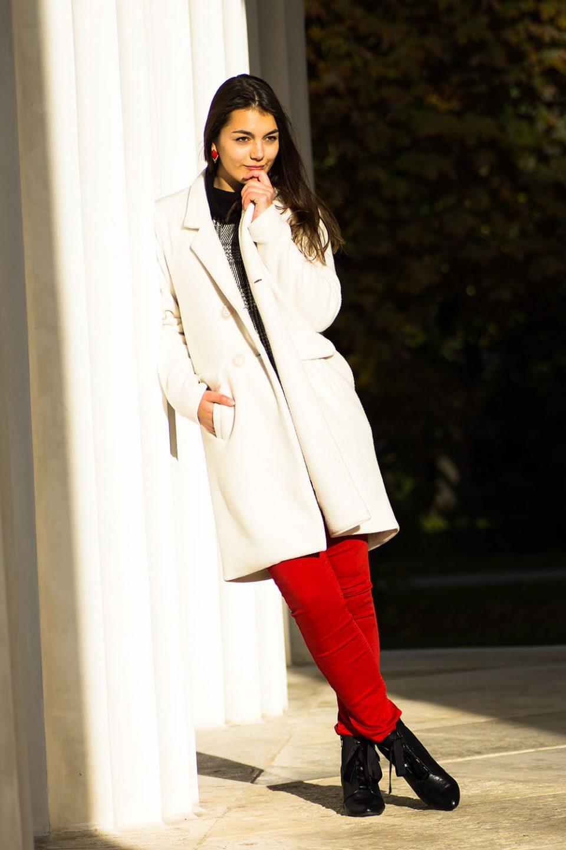 Dorie lehnt an einer Säule, trägt einen weißen Mantel, eine rote Hose von H&M, schwarze Stiefeletten von Mint&Berry und einen grauen Pullover