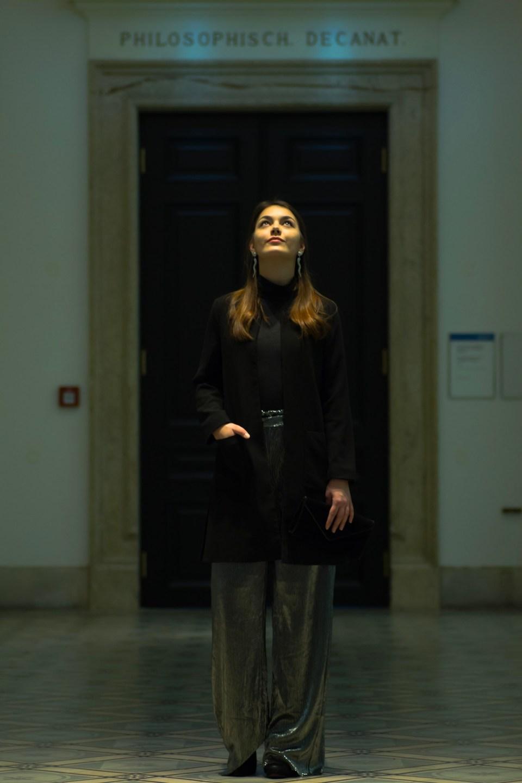 Dorie trägt ihr Silvester Outfit mit silberner Hose von Mango während sie in Lichtkegel schaut