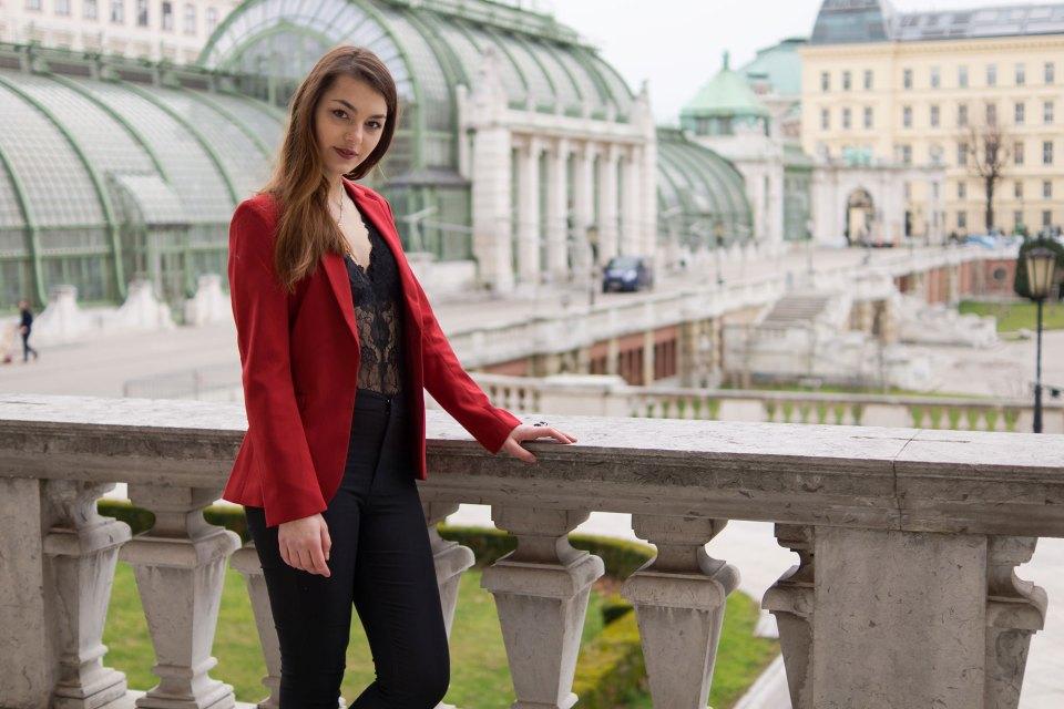 Dorie steht an der Brüstung im sexy Valentinstagslook mit rotem Blazer