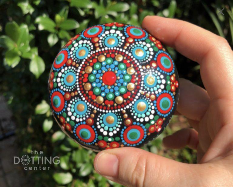 dot mandala on a wood pebble