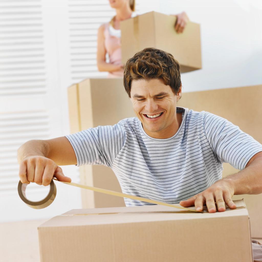 Photo: Smiling man packing box