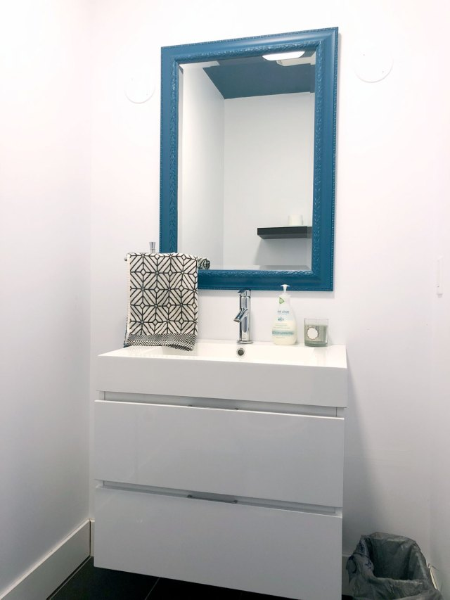 The powder room before. White vanity against white walls