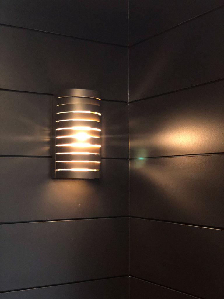Roswell 1 light halogen wall sconce from Kichler Lighting provides a beautiful ambient glow against the black shiplap walls