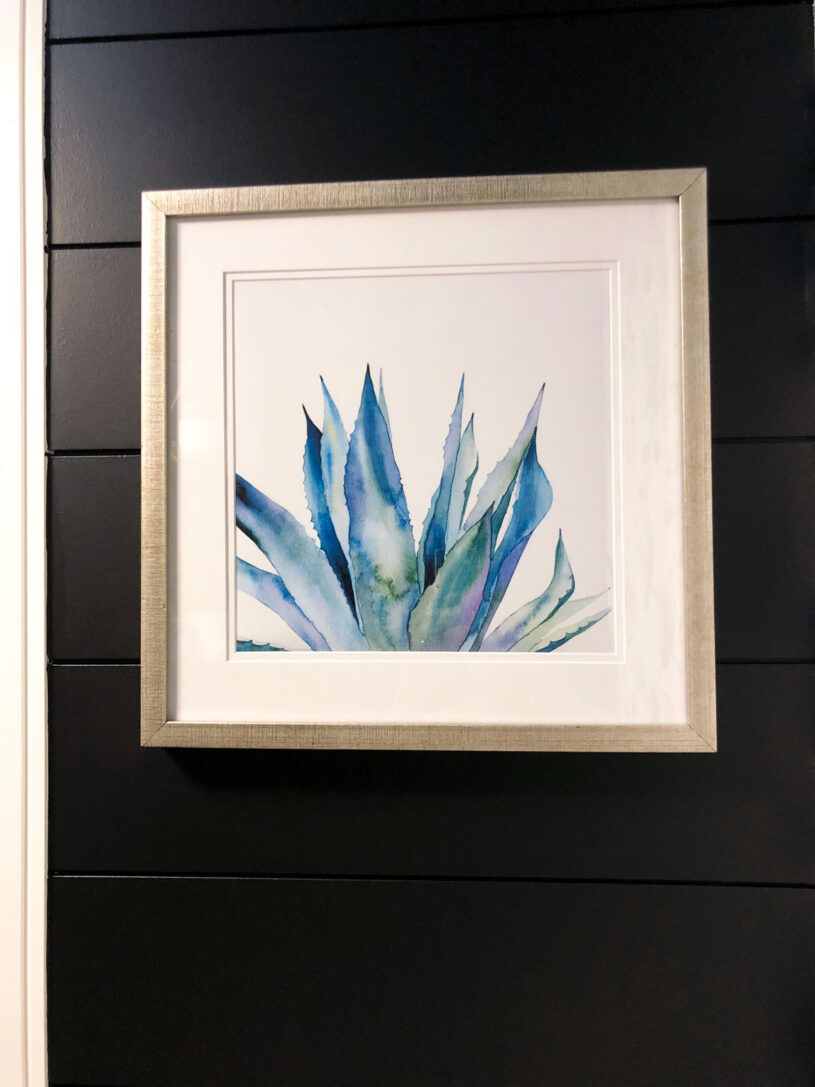 Artwork carries the colour from the wallpaper feature onto an adjacent wall