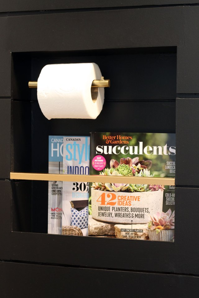 Magazines & toilet paper roll are inset into the shiplap wall in this stylish niche