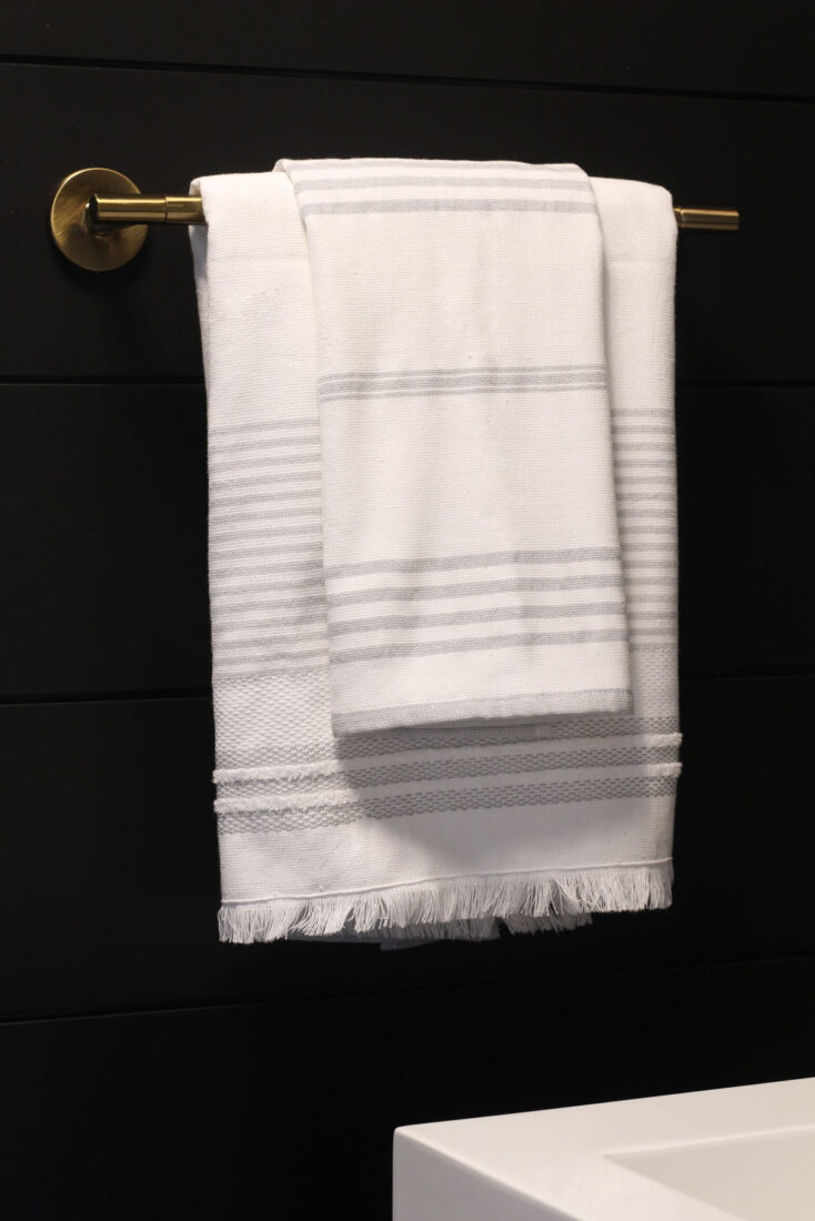 White striped towels are both functional and provide a perfect contrast to the black shiplap walls