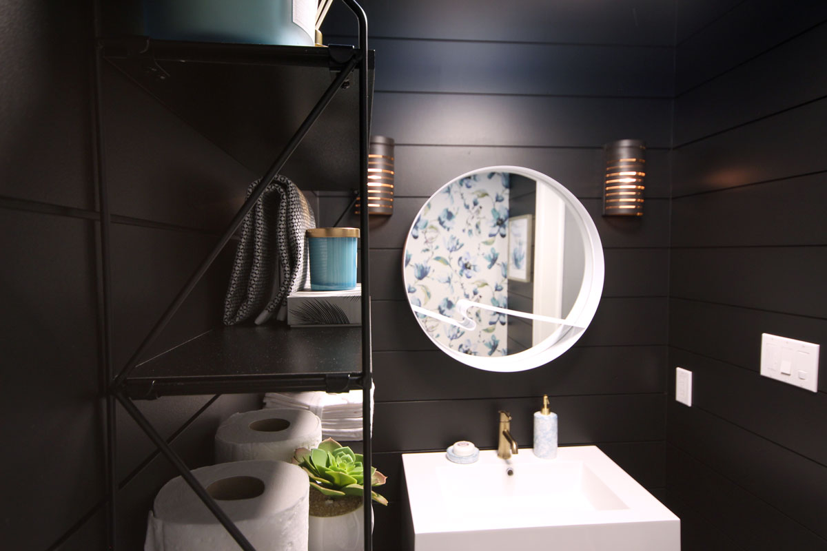 Our sleek and striking powder room reveal features black shiplap walls, a contrasting white vanity, a bold patterned fabric wallpaper feature and gold accents