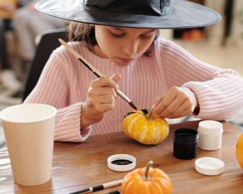 girl in pink painting a pumpkin