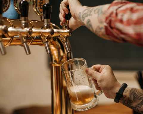 person pouring beer on clear drinking glass
