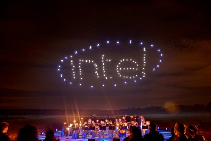 100 Intel drones fly at night as part of an outdoor flying drone light show syncopated to a live orchestra.