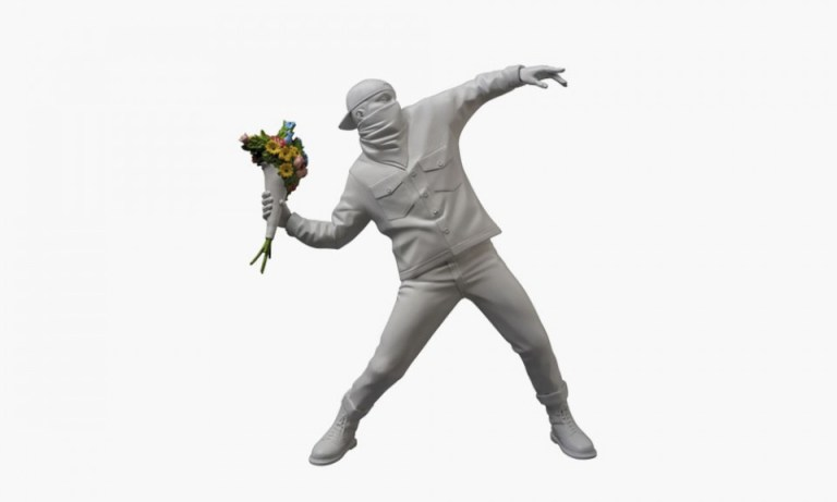 """Inspired by BANKSY's iconic """"Flower Bomber' artwork, Japanese brand Medicom Toy turned the work of art into a vinyl figure, sculptured by PERFECT-STUDIO. Standing 360mm tall, the figure comes in white, with only the flowers being colored. Famously the flowers are used as a weapon in the artwork. The limited edition art toy will release mid January 2016, with pre-orders open now."""