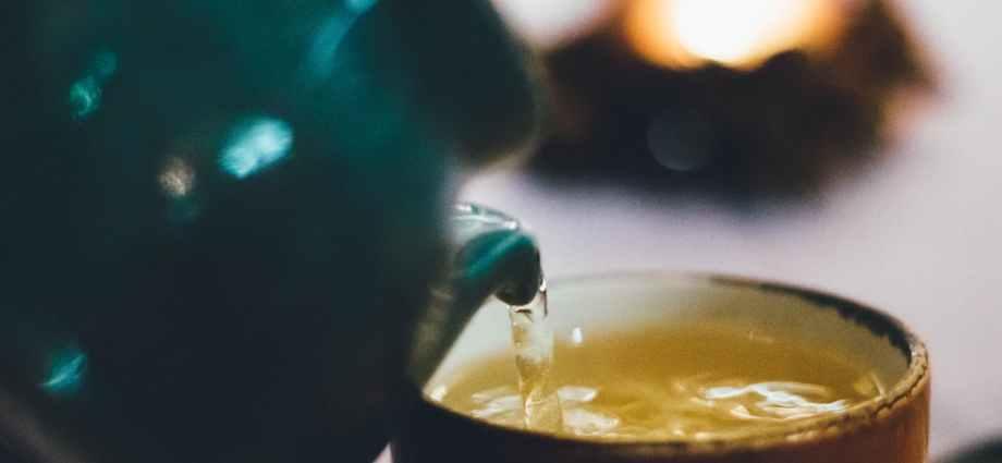 person pouring liquid into brown ceramic cup
