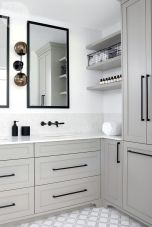 Simple Black and White mirrors and hard ware contrast the soft grey and whites in this bathroom.