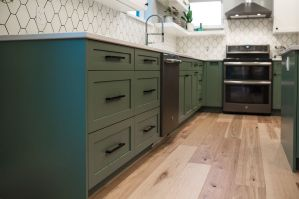The modern shaker cabinetry was painted green on the lowers and white up top and the corner was used to install a pair of corner floating shelves- perfect for plants and to allow for window placement and day light