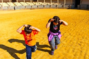 kids pretending to be bulls in bullfighting ring in Spain, Simple Joy: Kids' perspective, www.theeducationaltourist.com