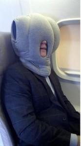 man on plane using ostrich pillow