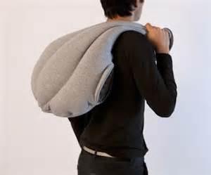 man using ostrich pillow as a bag thrown over shoulder