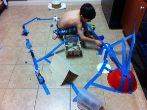 boy and car track made out of blue painter's tape, Choose the right toy, www.theeducationaltourist.com