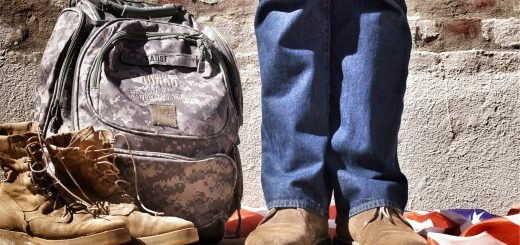 soldier standing next to backpack and boots