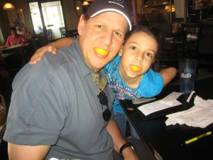 Dad and daughter with lemon slices in their mouths, Vacation Photo Tips, www.theeducationaltourist.com