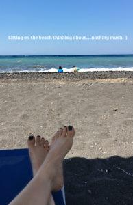 feet of mom watching 2 kids on the beach in Santorini