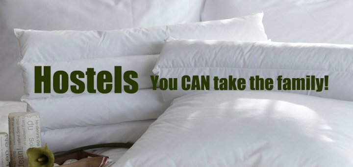 Bed with white linens and breakfast tray that says Hostels You can take the family. Www.theeducationaltourist.com