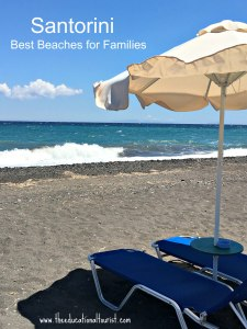 black sand beach in Santorini, Greece with blue lounge, black sand, and umbrella Best Beaches for family in Sanotorini