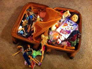 child's open suitcase with toys and dolls, suitcases for kids, www.theeducationaltourist.com