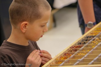 A boy carefully selects flies at the Fly Fishing Rendezvous