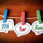 55329951-paper-speech-bubbles-with-text-2016-year-review-hanging-on-the-line-against-dark-wooden-background