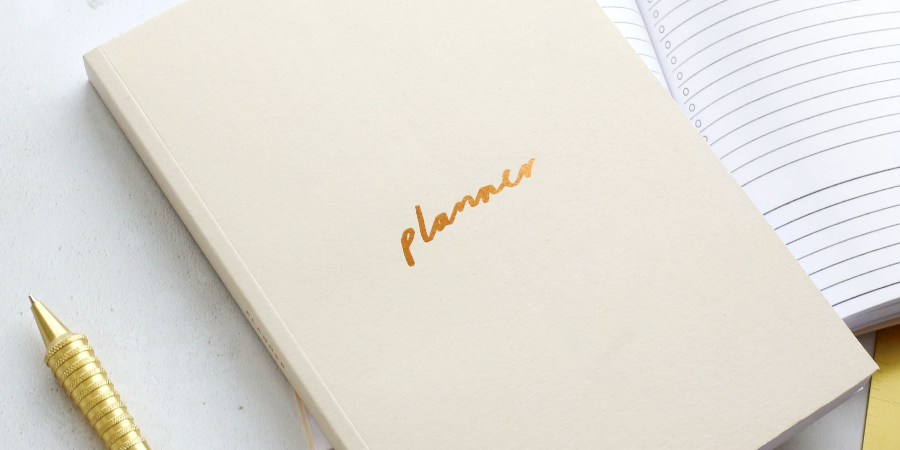 pale pink planner with a planner opened up beside it