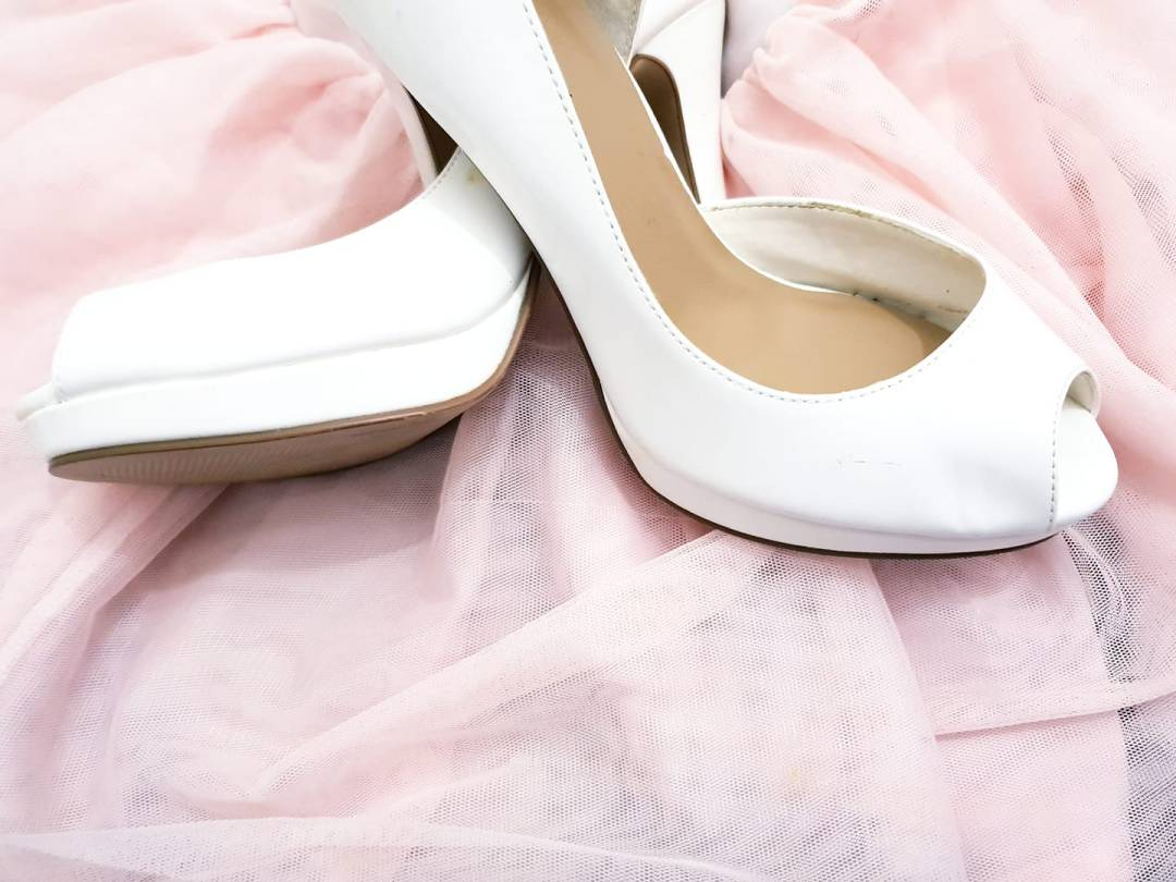 White wedding shoes on pink fabric