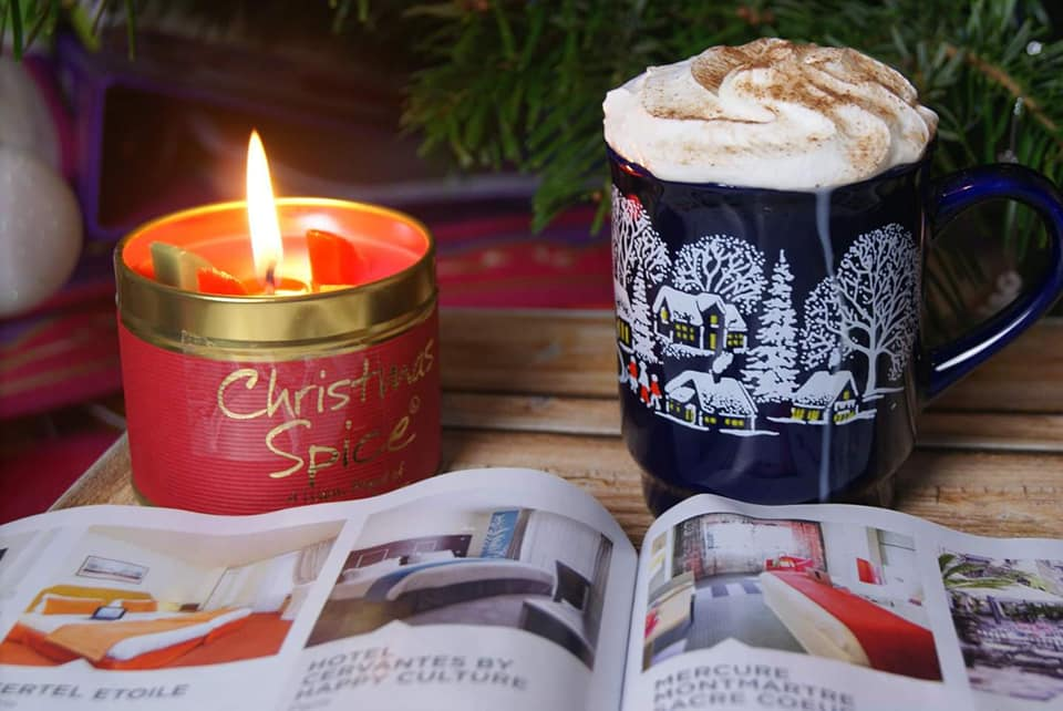 Hot chocolate with a candle burning in the backround with a holiday magazine open.