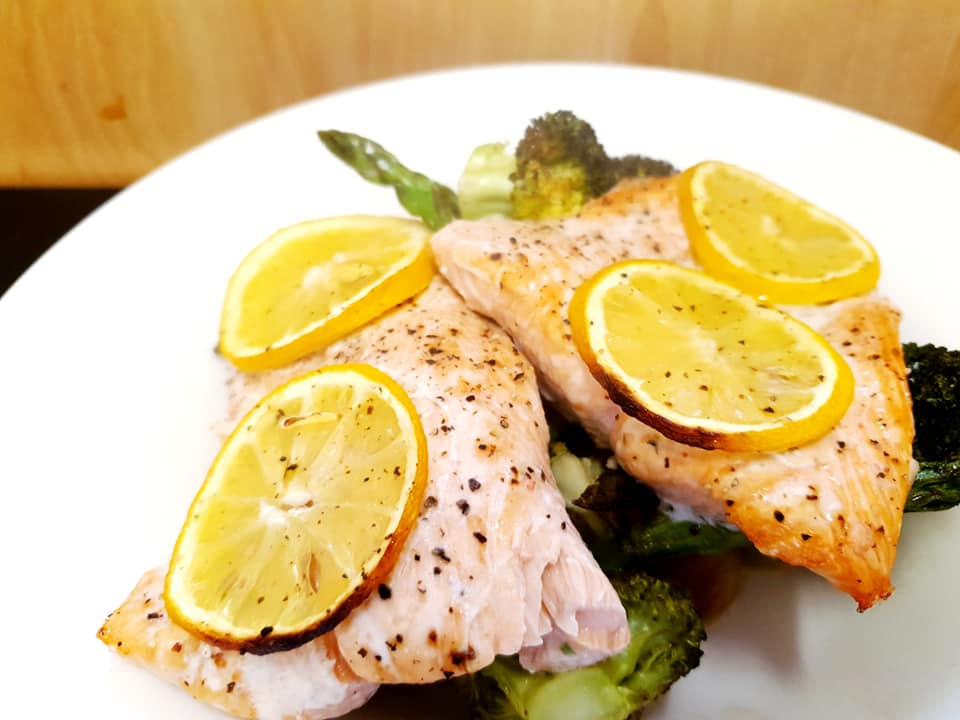 salmon on a bed of asparagus and broccoli, topped with lemon slices.