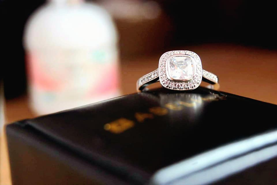 The ring sat on top of the jewellery box with a blurred perfume bottle in the background.