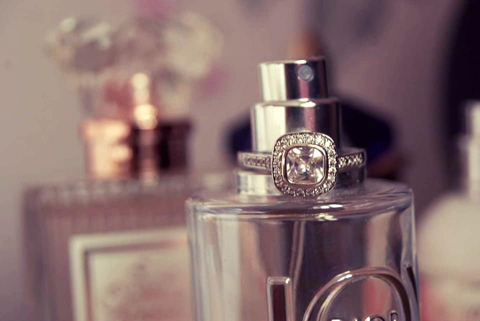 Square ring on top of a bottle of perfume.