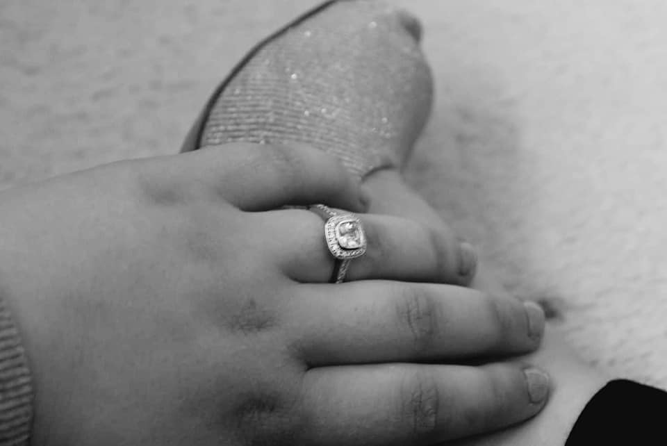 A black and white photo of my ring on my ring finger whilst i place my hand on my shoe.