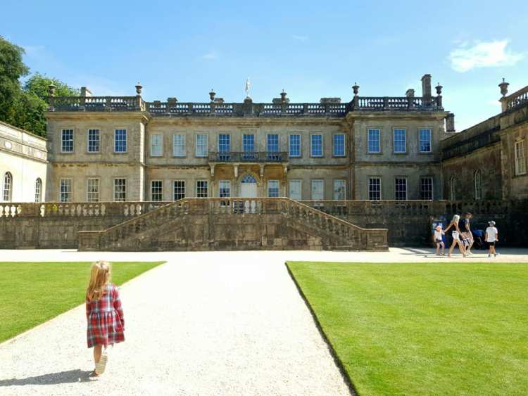 Shaniah walking down a gravelled path with Dyrham House infront of her.