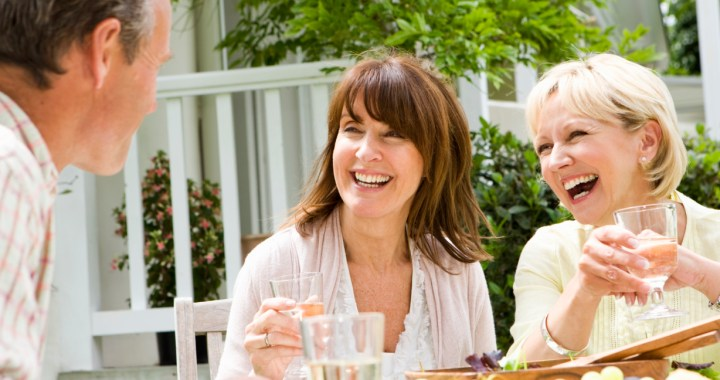Two women toasting a man while dining at an outside table