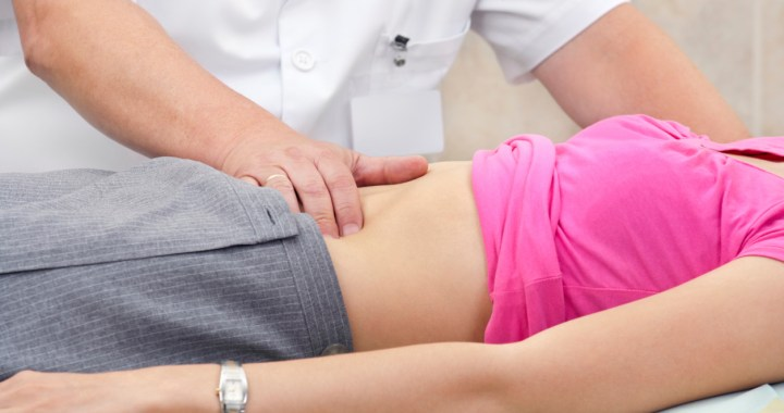 Woman on table having abdomen examined by physician