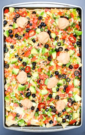 I've swapped some ingredients to lighten my 7-Layer Sheet Pan Nachos. This #recipe is #easy and versatile, so if you want to make changes, I say go for it! #healthyeats #vegetarian #sugarfree | theeverykitchen.com